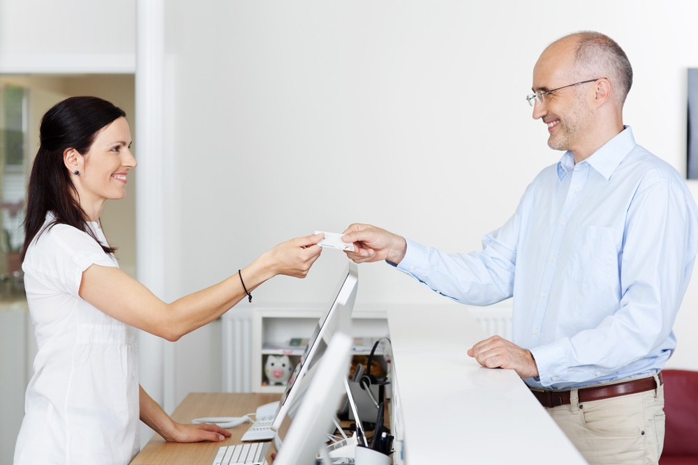 Mid adult female receptionist receiving card from patient in dentist clinic
